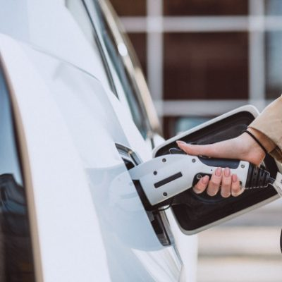 woman-charging-electro-car-electric-gas-station_1303-14656